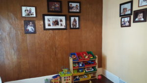 The children's toy area is adorned with family photos